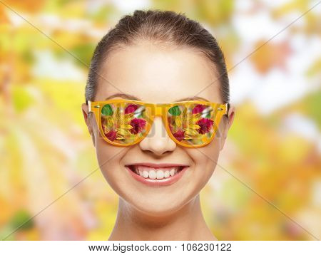 season and people concept - happy face of teenage girl in sunglasses with autumn leaves reflection o