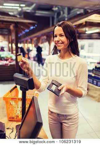 sale, shopping, consumerism and people concept - happy young woman with credit card and wallet buyin
