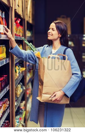 sale, shopping, consumerism and people concept - happy young woman with paper bag choosing and buyin