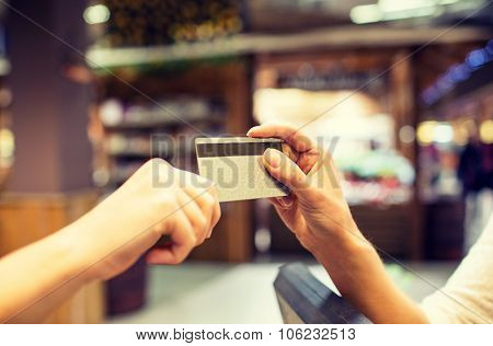 sale, shopping, payment, consumerism and people concept - close up of hands giving credit card at ch