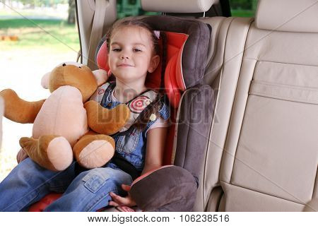 Cute little girl with teddy sitting in the car
