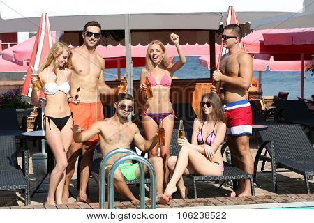Young people having fun on the beach near the swimming pool