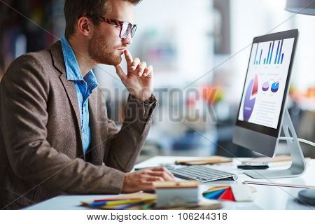 Young pensive businessman in eyeglasses working in office