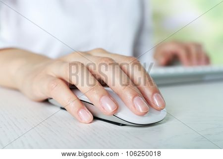 Female hand with computer mouse on table, closeup