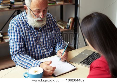 senior man explaining something and writing, young woman listening and looking at notepad at working