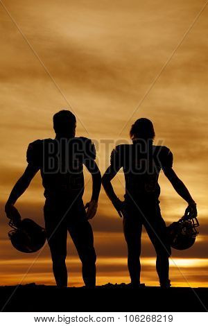 Silhouette Of Football Players Holding Helmets In The Sunset