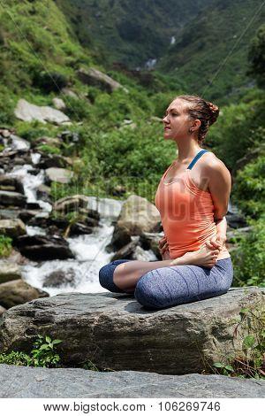 Young sporty fit woman doing yoga - meditating in Baddha Padmasana (Bound Lotus Pose) outdoors at tropical waterfall stock photo