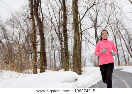 Winter cardio exercise - woman jogging doing her workout outside. Young adult running in outdoor par