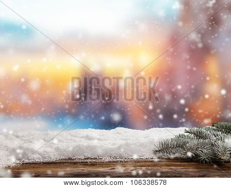 Winter background with pile of snow and blur evening landscape. Empty wooden planks on foreground. C