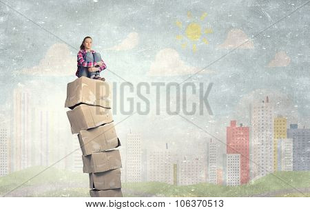 Smiling young woman sitting on stack of carton boxes