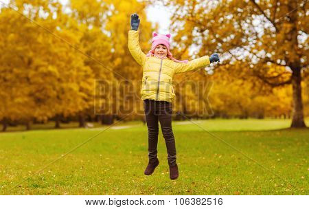 autumn, childhood, happiness and people concept - happy little girl with raised hands jumping and ha