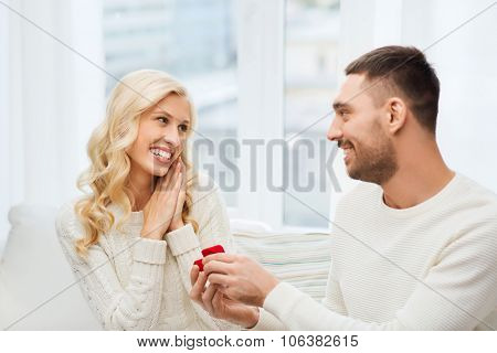 love, couple, relationship, proposal and holidays concept - happy man giving engagement ring in litt