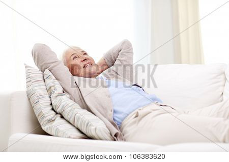 age, relax and people concept - happy smiling senior woman resting on sofa and dreaming at home