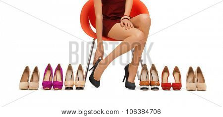 people, fashion, shopping, footwear and style - close up of woman sitting on chair and trying on hig
