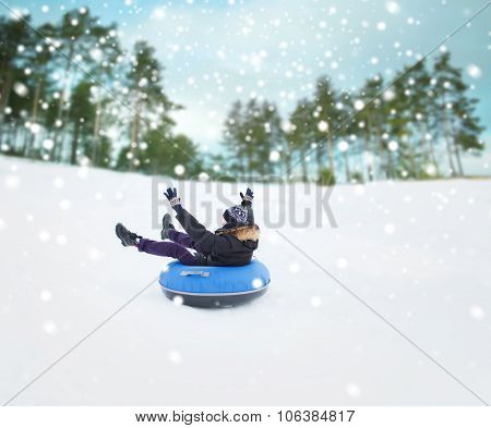 winter, leisure, sport, and people concept - happy teenage boy or young man sliding down on snow tub