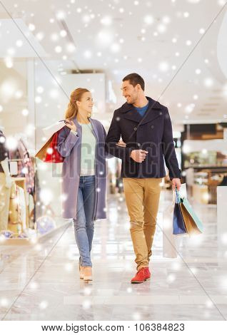 sale, consumerism and people concept - happy young couple with shopping bags walking and talking in
