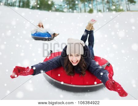 winter, leisure, sport, friendship and people concept - group of happy friends sliding down on snow
