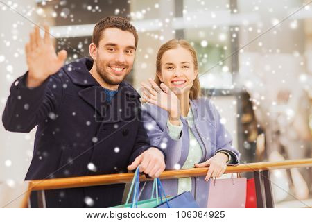 sale, consumerism, gesture and people concept - happy young couple with shopping bags waving hands i
