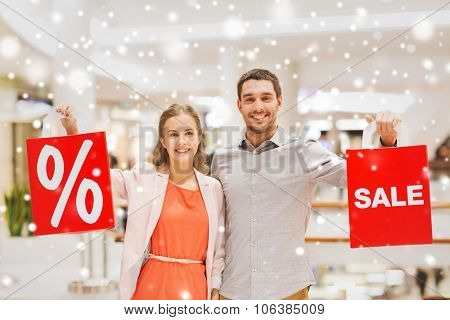 sale, consumerism and people concept - happy young couple with red shopping bags in mall with snow e