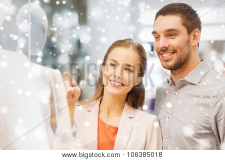 sale, consumerism and people concept - happy young couple pointing finger to shop window in mall wit