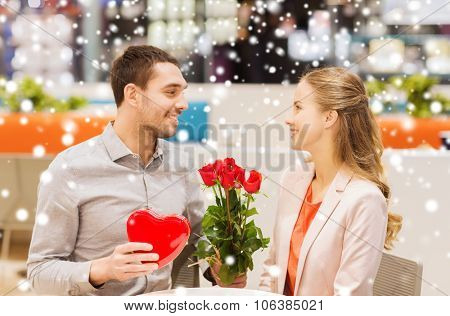 love, romance, valentines day, couple and people concept - happy young man with red flowers giving p