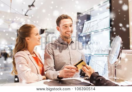 sale, consumerism, shopping and people concept - happy couple with credit card at jewelry store in m