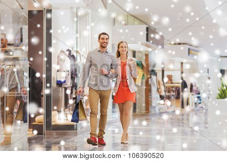 sale, consumerism and people concept - happy young couple with shopping bags walking in mall with sn