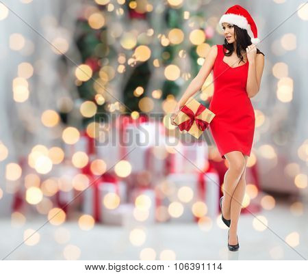people, holidays, christmas and celebration concept - beautiful sexy woman in red dress and santa ha