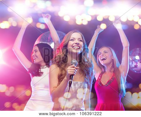 party, holidays, nightlife, entertainment and people concept - concept - happy women with microphone