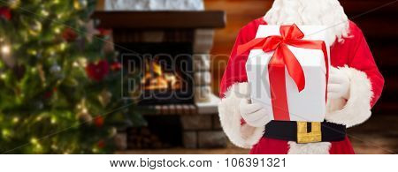 christmas, holidays and people concept - close up of santa claus with gift box over living room with