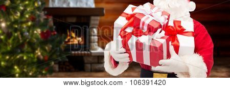 christmas, holidays and people concept - close up of santa claus with gift boxes over living room wi