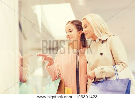 sale, consumerism and people concept - happy young women with shopping bags pointing finger to windo