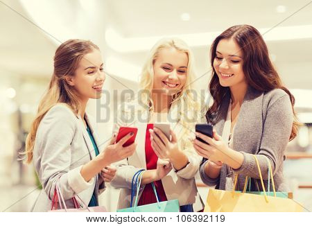 sale, consumerism, technology and people concept - happy young women with smartphones and shopping b