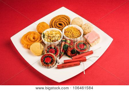 Diwali mithai like jalebi, bundi laddu, burfi and pera with Diwali snacks like chivda, sev, chakli served with Diwali firecrackers or fire crackers in a square white plate isolated on red background stock photo