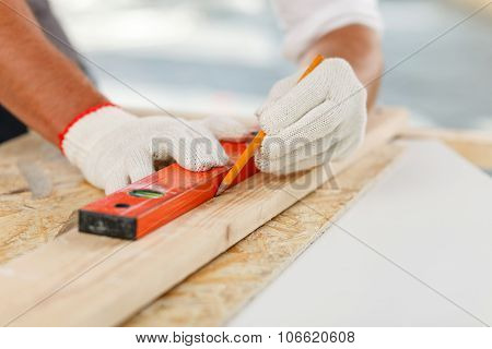 Close up of hands of carpenter taking measurements of wood board. The man is holding a ruler and drawing a line with a pencil stock photo