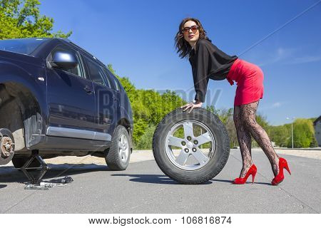 Lady dressed in provocative clubbing pantyhose and bright red shoes high heels mini skirt rolls large wheel car fixed on jack-screw with some tools stock photo
