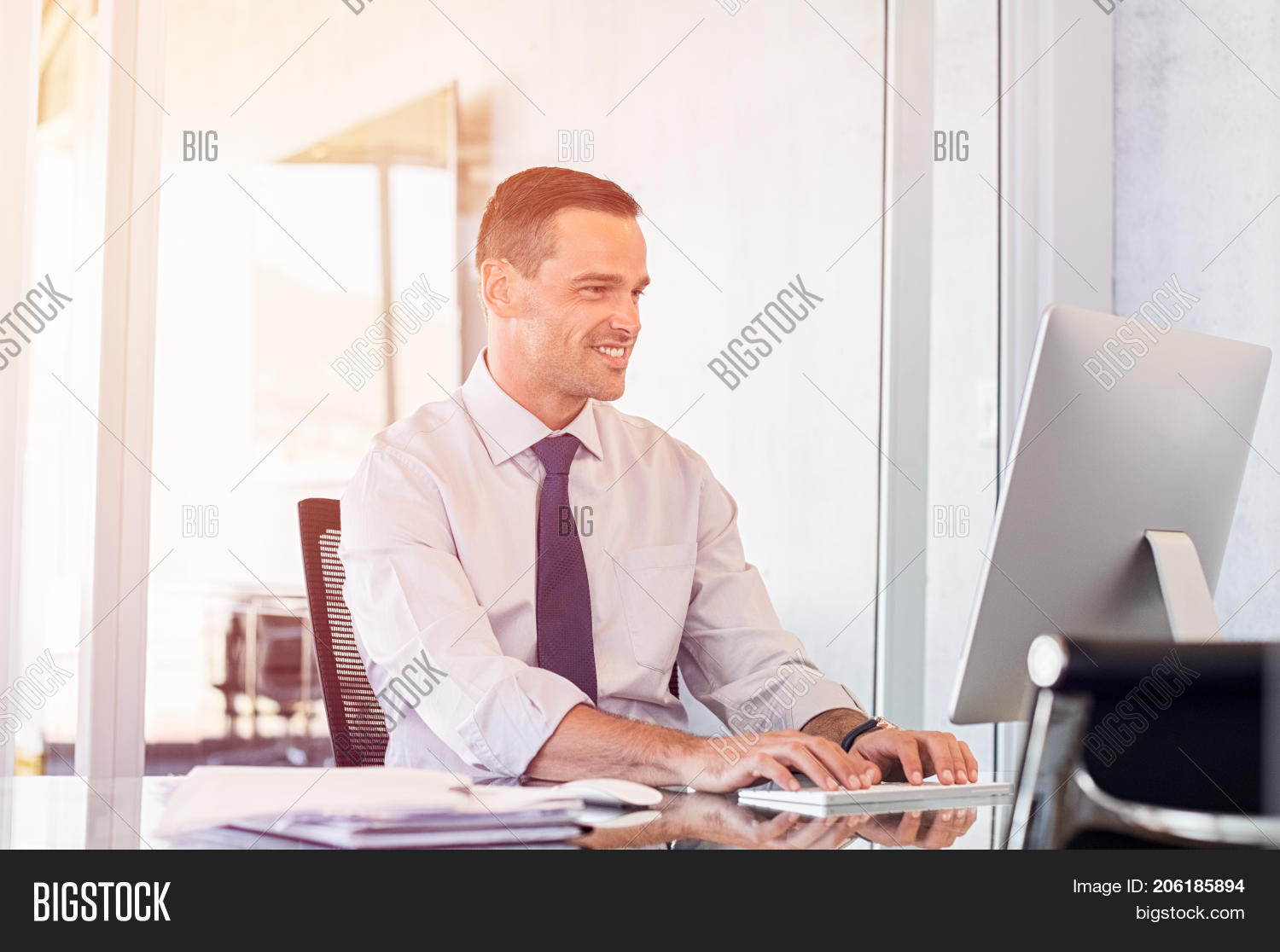 Young office businessman working on desktop computer. Smiling business man typing on keyboard at com