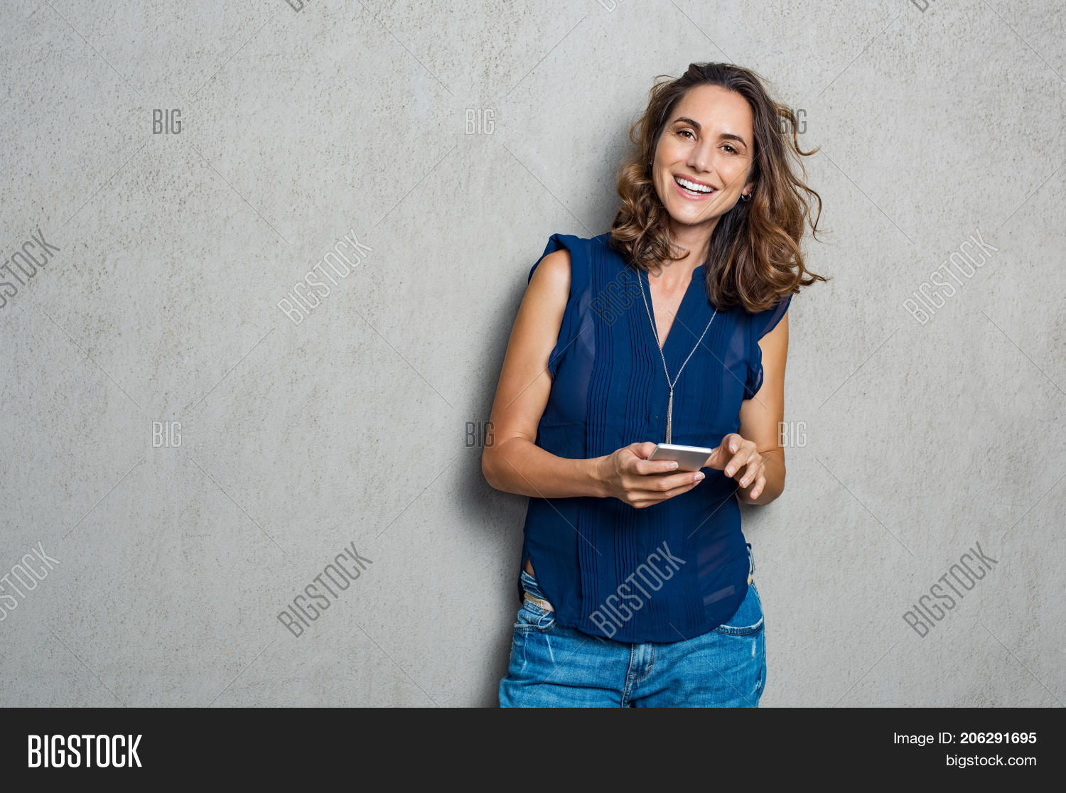 application,application mobile,background,beautiful woman,browsing,brunette woman,carefree woman,casual woman,cellphone,communication,connection,connection concept,copy space,gray background,grey background,happy,happy woman,hispanic,hispanic woman,holding,internet,internet technology,isolated,joy,latin,latin woman,laughing,looking,looking at camera,mature,message,messaging,mid adult woman,mobile,mobile phone,network,phone,smart,smart phone,smartphone,smile,smiling woman,technology,texting,typing,typing on phone,using,wireless,woman