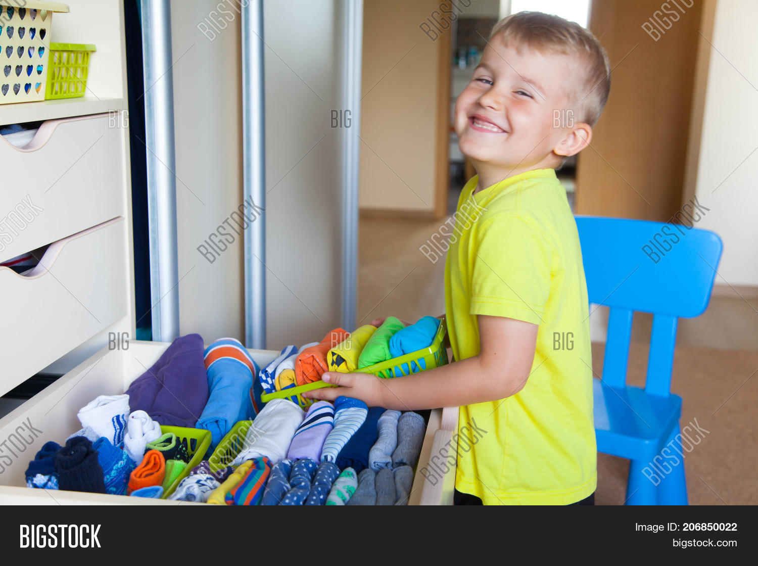 The Child Puts His Clothes On. The Boy Pulls The T-shirt Out Of The Closet.