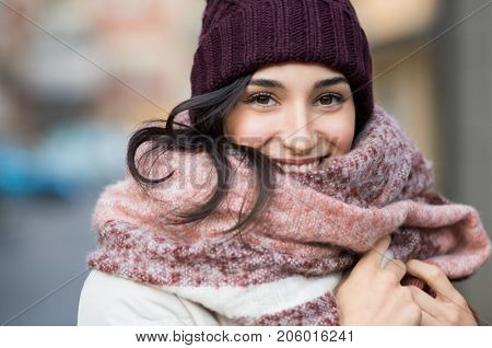 Closeup face of a young happy woman enjoying winter wearing scarf and cap. Smiling girl in a colorfu