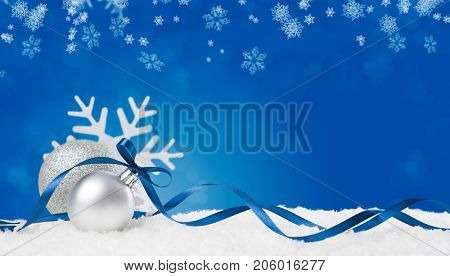 Christmas background in blue. Snow flakes and christmas balls with ribbon and copyspace. Xmas backgr