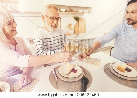 Our little tradition. Cheerful retired couple sitting at the table with their adult son while drinking wine and enjoying celebration stock photo