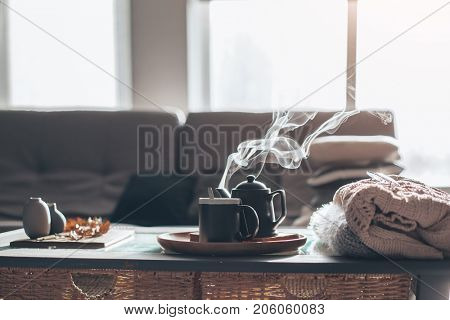 Still life details in home interior of living room. Sweaters and cup of tea with steam on a serving