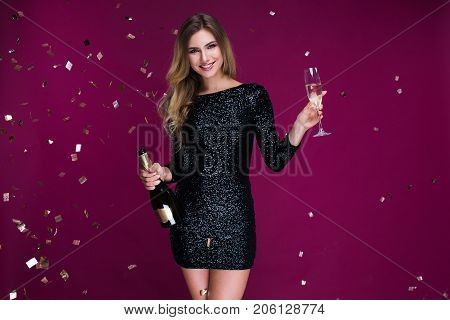 Happy New Year to you! One beautiful young woman with confetti, celebration Christmas with bottle and glass of champagne. New Year's party. Christmas Eve. stock photo