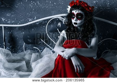 Santa muerte girl with red flower diadem is sitting on the bed holding red dress in her hands