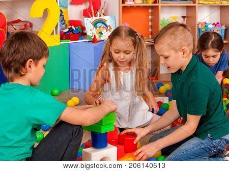 Children building blocks in kindergarten. Group kids playing toy on floor. Top view of interior pres