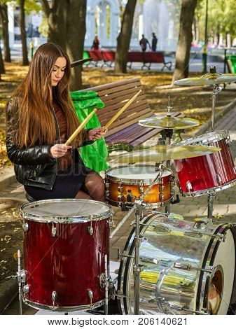 Festival music band in autumn park. Sad woman playing on percussion instruments in city park. Girl is playing drums. stock photo