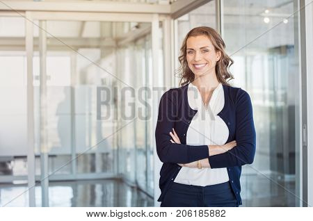 Portrait of mature beautiful business woman in the office looking at camera. Business executive stan