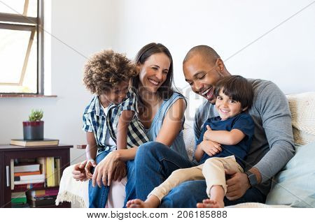 Happy multiethnic family sitting on sofa laughing together. Cheerful parents playing with their sons
