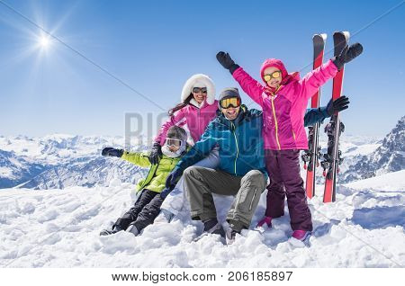 Laughing family in winter vacation with ski sport on snowy mountains. Happy man and woman with sons